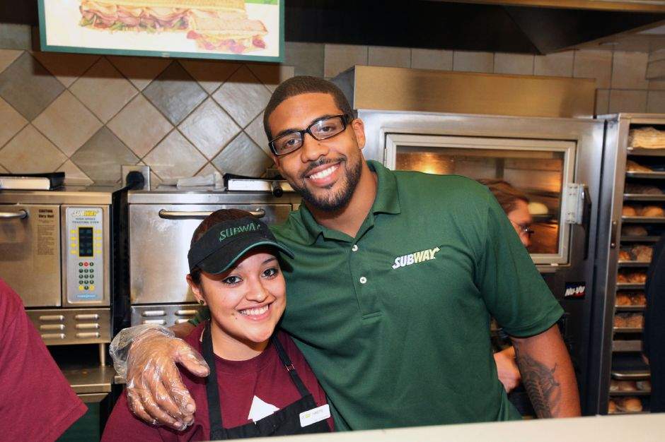 Houston football star Arian Foster, left, and a SUBWAY employee prepare BBQ Pulled Pork sandwiches for fans at a SUBWAY restaurant at the SUBWAY All-Star BBQ on Wednesday, July 13, 2011, in Los Angeles. The event marked the launch of the sandwich chain