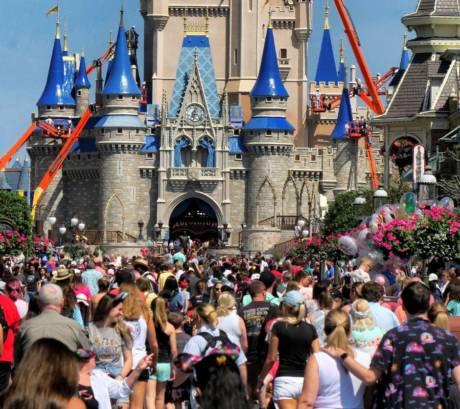 FILE - In this March 12, 2020, file photo, a crowd is shown along Main Street USA in front of Cinderella Castle in the Magic Kingdom at Walt Disney World in Lake Buena Vista, Fla. As Walt Disney World prepares to allow some third-party shops and restaurants to open at its entertainment complex later this week, it