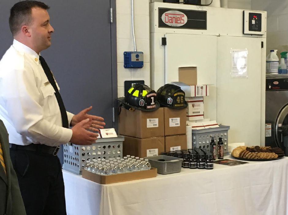 North Haven Fire Chief Paul Januszewski accepts a donation of on-scene decontamination wipes from a local woman at the North Haven Fire Department on March 4, 2018. | Lauren Takores, Record-Journal
