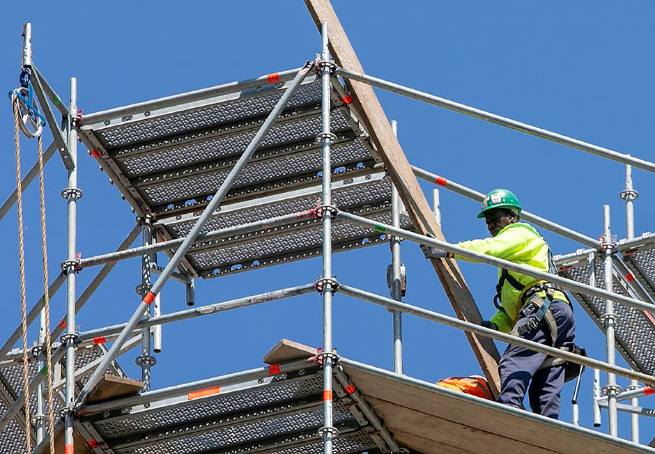 A worker lifts a board from a platform as crews from West Hartford based Advanced Scaffold Services dismantle the smokestack of the former Meriden-Wallingford Hospital on Cook Avenue in Meriden, Thursday, August 23, 2018. Dave Zajac, Record-Journal