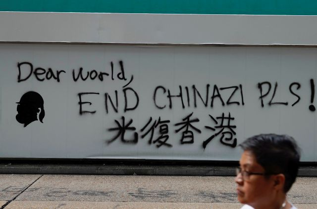 "A man walks past a wall with the words ""Liberate Hong Kong- Dear World End Chinazi Please"" in Hong Kong, Monday, Oct. 7, 2019. Tens of thousands of masked protesters marched defiantly in the city center Sunday, but the peaceful rallies quickly degenerated into chaos at several locations as hard-liners again lobbed gasoline bombs, started fires and trashed subway stations and China-linked banks and shops. (AP Photo/Vincent Yu)"