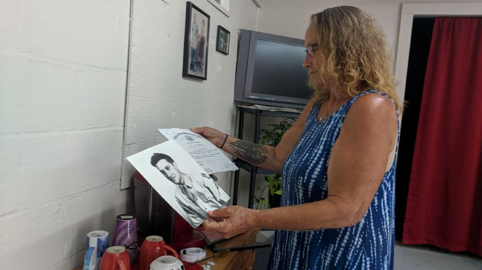 Maria Mazzacane Perez shows a photo of her father, Joseph Mazzacone, and his U.S. Army discharge certificate, before she frames and hangs them up on one of the walls at Cheshire Barber Shop. Mazzacane Perez reopened the shop this week, after it had been closed for more than two months. | Michael Gagne, Record-Journal