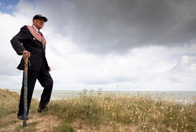 World War II D-Day veteran and Penobscot Elder from Maine, Charles Norman Shay poses on the dune overlooking Omaha Beach prior to a ceremony at his memorial in Saint-Laurent-sur-Mer, Normandy, France, Friday, June 5, 2020. Saturday