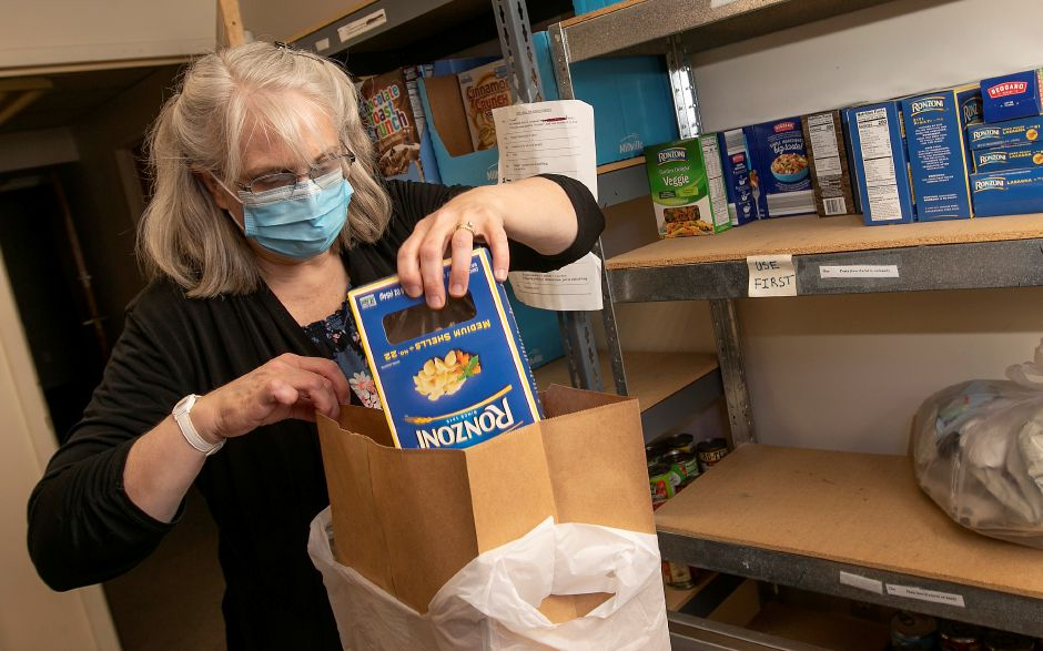 Volunteer Martha Murphy, of Meriden, packs food items for city residents who are enduring food insecurity at Ted's Kitchen at St Andrew