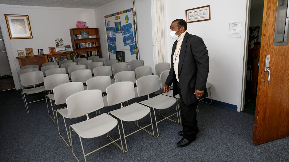 At left: Pastor Willie Young walks through a worship room at Mount Hebron Baptist Church at 84 Franklin St., Meriden, on Friday. A COVID-19 vaccination clinic was held on Saturday, March 6, at the church. The chairs pictured were set to be spaced out in accordance with COVID-19 guidelines for the clinic.