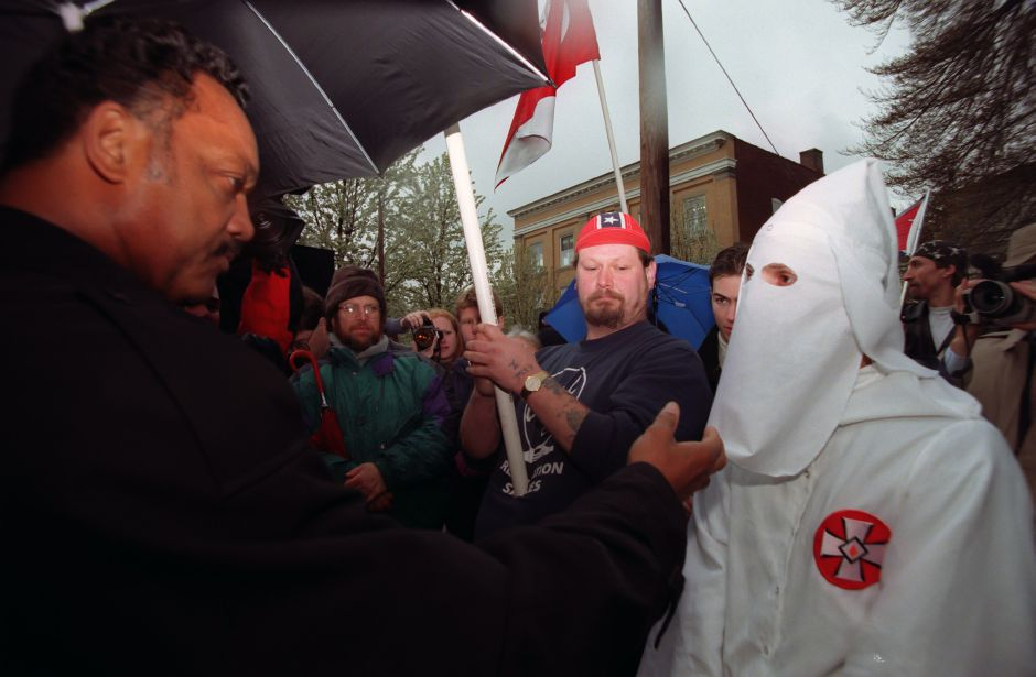 The Rev. Jesse Jackson tries to lift the hood off Klu Klux Klan member Mike Akia, from Milford, during a protest of Jackson