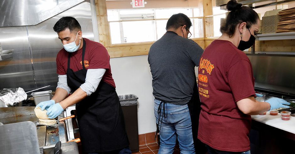 Chef Daniel Torres, left, starts an order during the lunch rush on Wednesday at the new Tacos Mi Nacho at 1796 Meriden-Waterbury Turnpike in Southington. Tacos Mi Nacho's second location opened on Monday. Photos by Dave Zajac, Record-Journal
