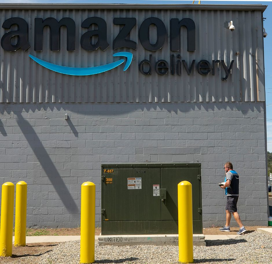 An Amazon employee talks on a cell phone outside the new Amazon Logistics at 425 S. Cherry St. in Wallingford, Wed., Aug. 26, 2020. Amazon Logistics is a shipping and delivery service that uses third-party contractors to pick up and deliver customer orders. Dave Zajac, Record-Journal