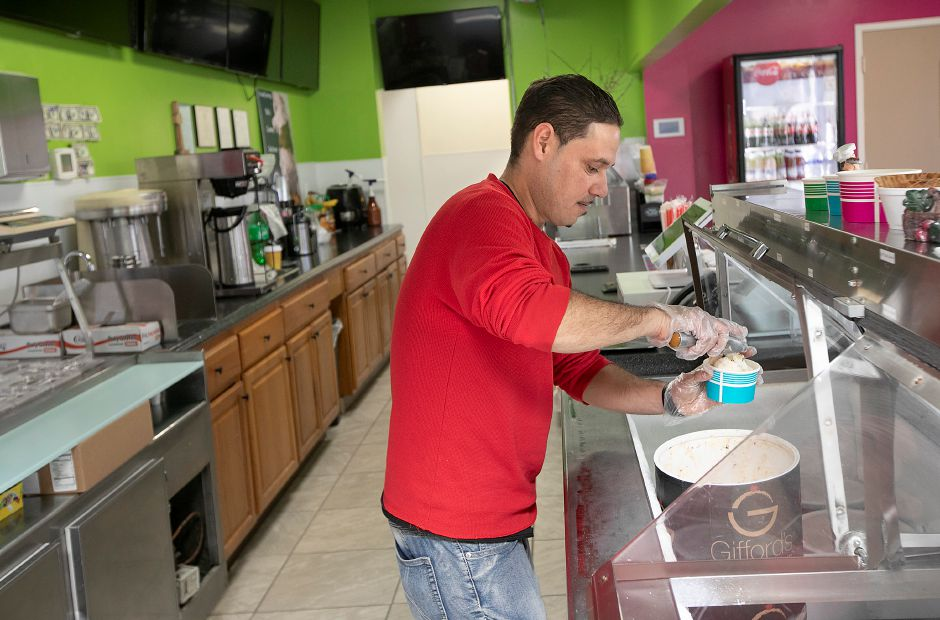 Downtown Freezy Freezes Gamestop co-owner Alex Ortiz prepares a cup of chocolate chip ice cream at the 55 W. Main St. business in Meriden, Wed., Feb. 19, 2020. The business now features ordering through Uber Eats. Dave Zajac, Record-Journal