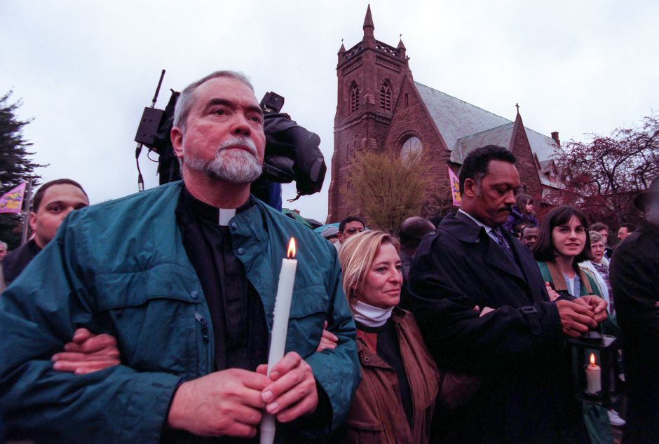 The Rev. Brendan McCormick, left, walks arm in arm with Donna Howard, center, of Wallingford, and Rev. Jesse Jackson, right, after Jackson