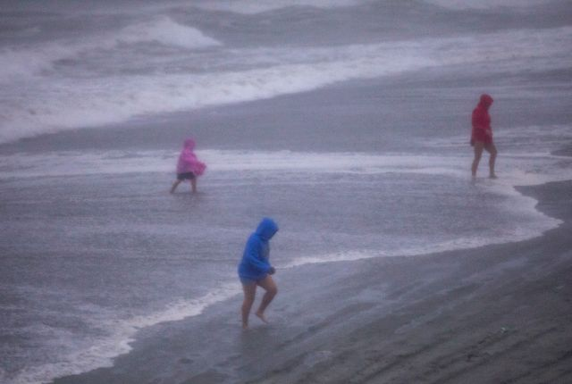 People walk on the beach in Garden City, S.C., as Isaias approached the Carolinas on Monday, Aug. 3, 2020. (Jason Lee/The Sun News via AP)