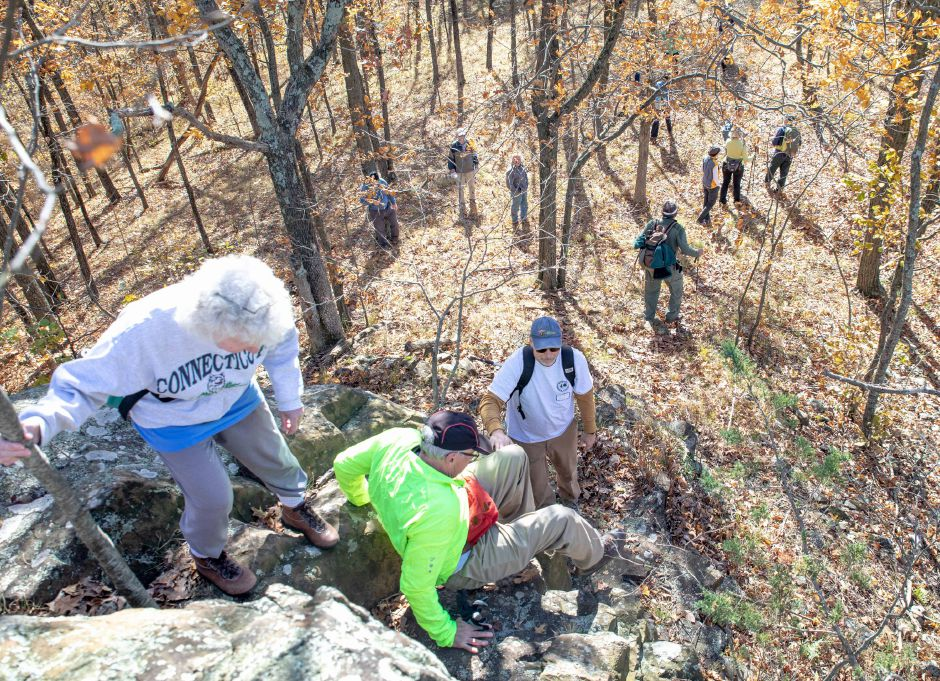 Berlin Land Trust member Raymond Archacki assists hikers down a rock outcropping while on a trek to Lamentation Mountain