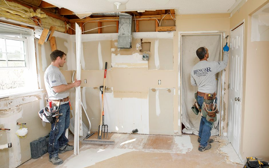 Above: Carpenters for Wallingford based Bencar Building Systems LLC, Cody Benson, left, and Craig Agro remove door trim on Tuesday as part of a kitchen makeover at a residence on High Hill Road in Wallingford.