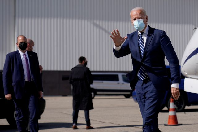 Democratic presidential candidate former Vice President Joe Biden waves as he arrives at Detroit Metropolitan Wayne County Airport, Friday, Oct. 16, 2020, in Detroit. (AP Photo/Carolyn Kaster)