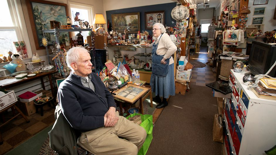 Allen Weathers watches a news program on a monitor as he and wife Neda wait for customers inside their Fair Weather Antiques shop at 763 Hanover Road in Meriden on Friday. Local, state and federal agencies are investigating after a man was found dead in an apartment containing hazardous chemicals above the shop.Dave Zajac, Record-Journal
