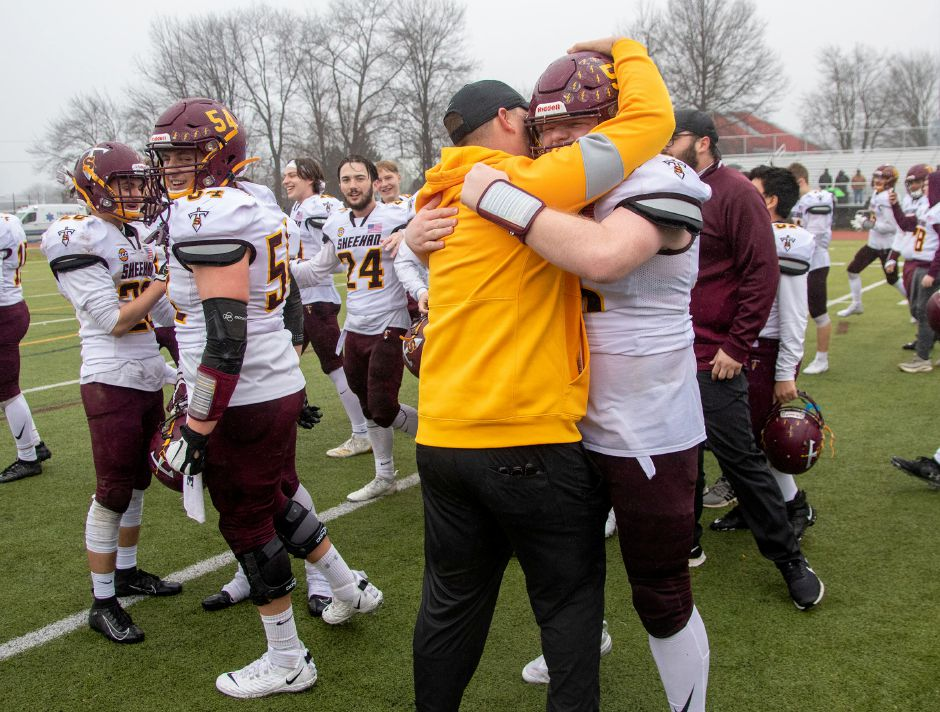 Sheehan head coach John Ferrazzi embraces senior lineman Mickey Deming after the Titans defeated defending champ Bloomfield 64-33 in the CIAC Class S state final Saturday at Trumbull High School. Aaron Flaum, Record-Journal