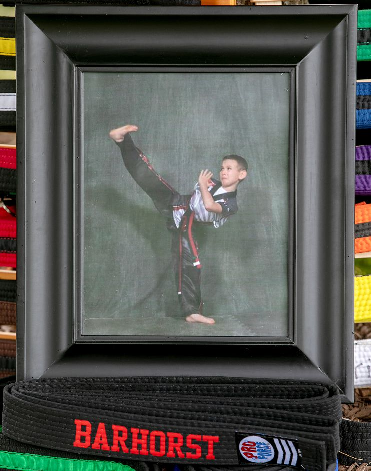A picture of Tristan Barhorst rests on June 24  on a black belt given to the family in his honor. Tristan, 10, was struck and killed by a passing vehicle after buying ice cream from an ice cream truck on Friday, June 12. Tristan was a standout student at Leadership Martial Arts in Southington. Instructor Rick Griffin presented the family the honorary black belt and a karate scholarship fund has been set up in his memory.