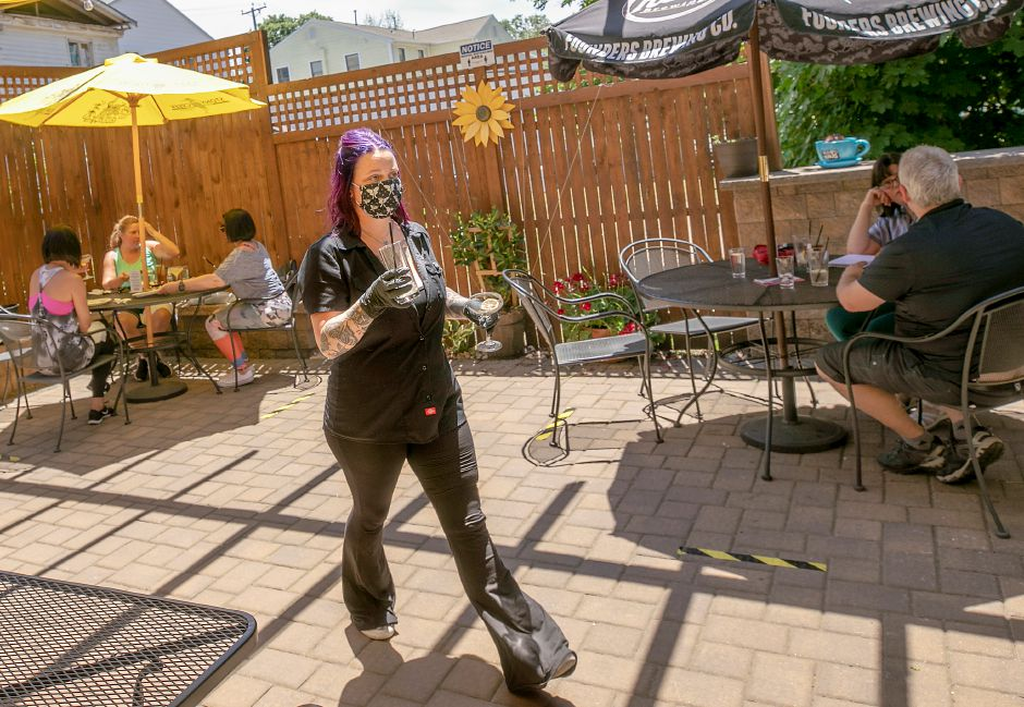 Katie Kennedy, manager, walks through the Hop Haus patio after clearing a table for customers at the 28 W. Main St. restaurant in Plantsville, Thurs., Jun. 25, 2020. Dave Zajac, Record-Journal