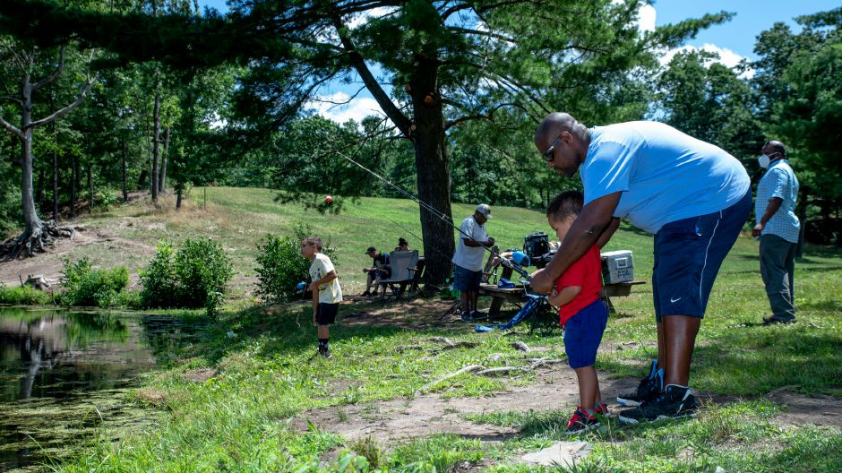 Phillip Dozier Jr. shows his son, Kian Dozier, how to fish Sunday at Wharton Brook State Park in North Haven. Even with sunny and warm weather, visitors remained sparse as the coronavirus pandemic remains a concern. Devin Leith-Yessian, Record-Journal