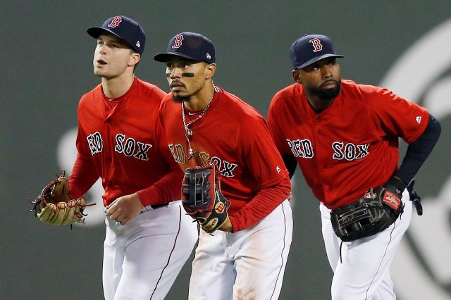 In this April, 12, 2019, photo, Andrew Benintendi, Mookie Betts and Jackie Bradley Jr., left to right, run in after defeating the Orioles at Fenway Park. Associated Press