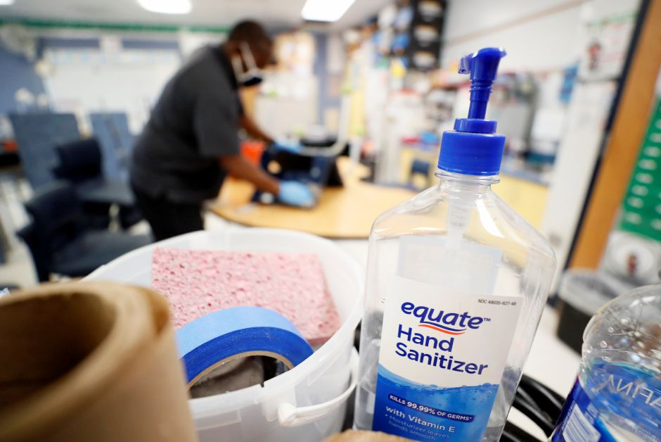 A bottle of hand sanitizer sits on a cart as Des Moines Public Schools custodian Tracy Harris cleans a chair in a classroom at Brubaker Elementary School, Wednesday, July 8, 2020, in Des Moines, Iowa. School districts that plan to reopen classrooms in the fall are wrestling with whether to require teachers and students to wear face masks. In Iowa, among other places, where Democratic-leaning cities like Des Moines and Iowa City have required masks to curb the spread of the...