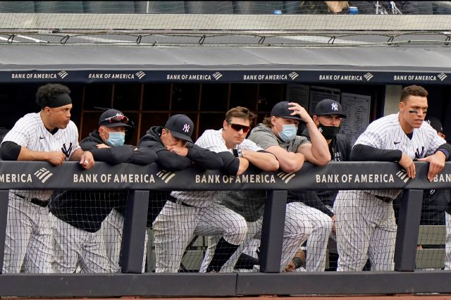 New York Yankees players lean on the dugout railing during the seventh inning of a loss to the Tampa Bay Rays in a baseball game, Sunday, April 18, 2021, at Yankee Stadium in New York. From left to right, are: designated hitter Giancarlo Stanton, outfielder Brett Gardner, who did not play Sunday, retiring outfielder Jay Bruce, DJ LeMahieu, injured first baseman Luke Voit, a coach and Aaron Judge. (AP Photo/Kathy Willens)