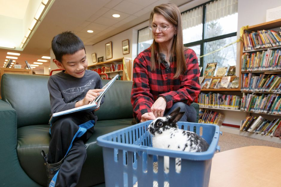 "Max Massameno, 6, reads  ""Spot"" with Aili McKeen, both of Wallingford, on April 4,  2018, during Books and Bunnies in the children's section of the Wallingford Public Library."