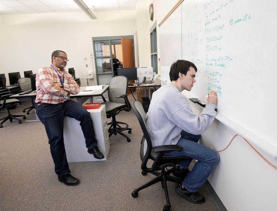 Alex Cable, 26, works on a problem in an Intermediate Algebra class with math professor Mohamed Mountassir, left, at Tunxis Community College in Farmington on March 12. Alex is one of hundreds of young adults with autism in Connecticut that cannot receive support services from the state due to a lack of funding and a wait list exceeding 1,600 people. Alex is attending Tunxis Community College in hopes of one-day getting a full-time job. Dave Zajac, Record-Journal