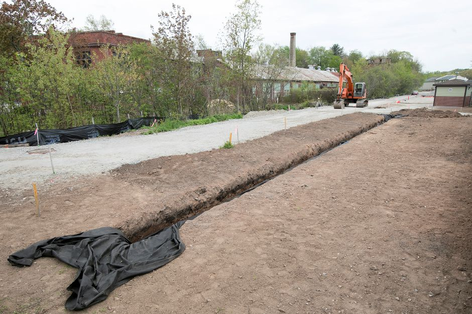 Crews continue work on a new section of the Farmington Canal Heritage Trail between Cornwall Avenue and West Main Street in Cheshire, Thursday, May 10, 2018. New restrooms, top right, have been constructed near the West Main Street entrance. Dave Zajac, Record-Journal
