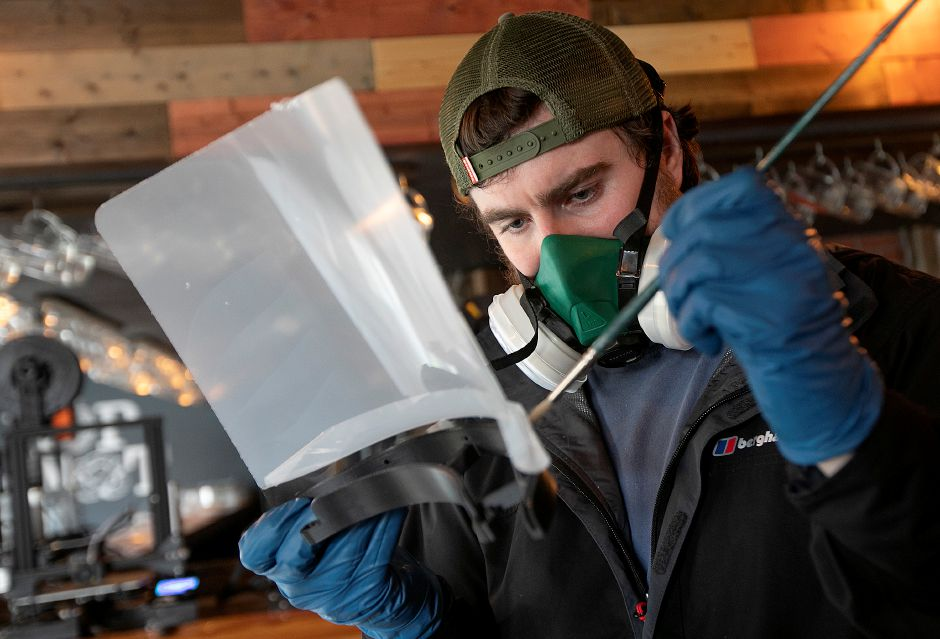 Nikolas Thomson bonds a shield to a 3-D printed frame while making face shields for health care workers and first responders.