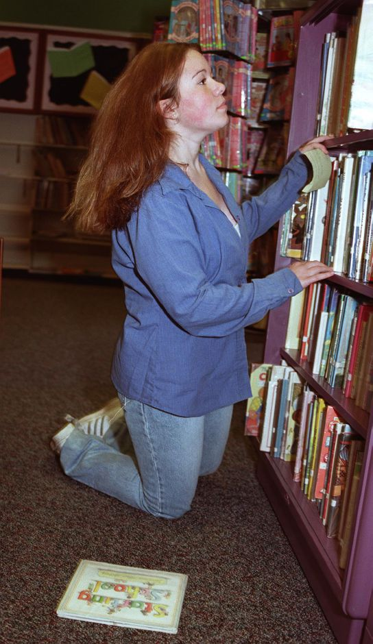 Jessica Wenek, 14, looks for a book in the children
