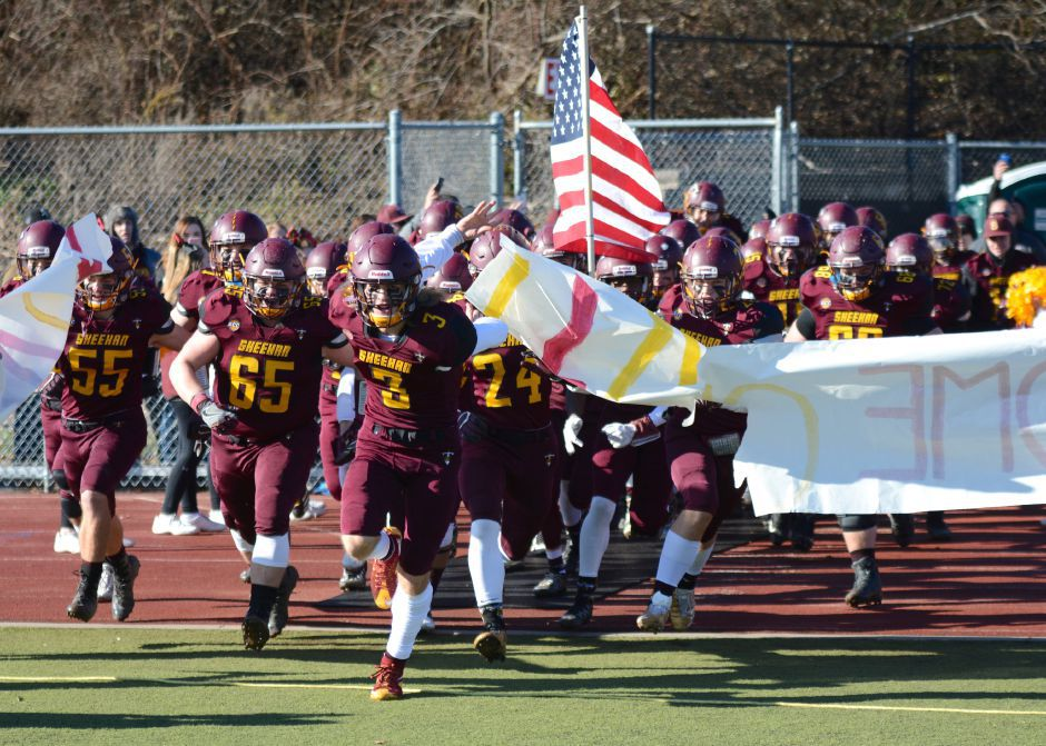 Wes Terzi, of Sheehan, leads the Titans out in the team's annual Thanksgiving Day football game against Lyman Hall on Thursday, Nov. 23, 2017. The Titans defeated the Trojans, 49-20. | Bryan Lipiner, Record-Journal