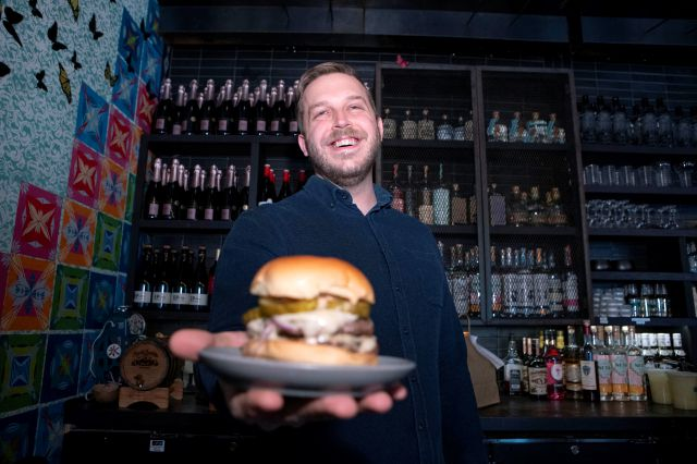 Josh Phillips, the co-owner of Espita, a stylish Mexican restaurant, holds a Ghostburger at his restaurant in downtown Washington, Monday, Feb. 15, 2021. Phillips opened a delivery-only brand called Ghostburger in August to keep Espita's kitchen running through the winter. He chose burgers because he wanted to reach new customers at a lower price point than Espita. It's been so successful that Phillips is now scouting for locations for standalone Ghostburger restaurants. (AP Photo/Jose...