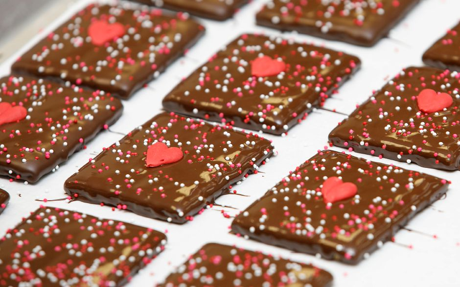 Graham crackers dipped in chocolate with candy sprinkles and hearts for Valentine