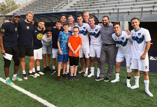 Sam Hayden, center right, and his brother Luke pose with the Quinnipiac University men's soccer team. Submitted photo.