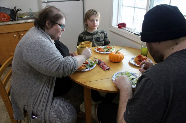 FILE: Airis Messick, left, and Brian Messick, right, eat lunch with this 9-year-old son, Jayden, at their apartment in Anchorage, Alaska, on Wednesday, Nov. 11, 2020. (AP Photo/Mark Thiessen)