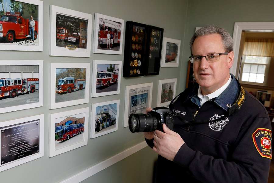 Michael Quinn, attorney, state representative and fire photographer hobbyist, holds a Nikon SLR he uses to capture fires on ride-alongs with the city