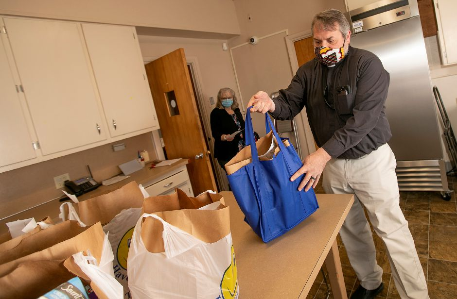 Rev. Mark Byers, right, helps out volunteer Martha Murphy, of Meriden, with bags of food at Ted's Kitchen at St Andrew's Episcopal Church in Meriden on Wednesday.
