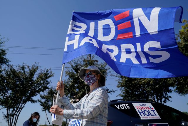 A Michell Rawlins shows her support of Democratic presidential candidate former Vice President Joe Biden by holding a flag in the wind Sunday, Oct. 11, 2020, in Plano, Texas. Democrats in Texas are pressing Joe Biden to make a harder run at Texas with less than three weeks until Election Day. (AP Photo/LM Otero)