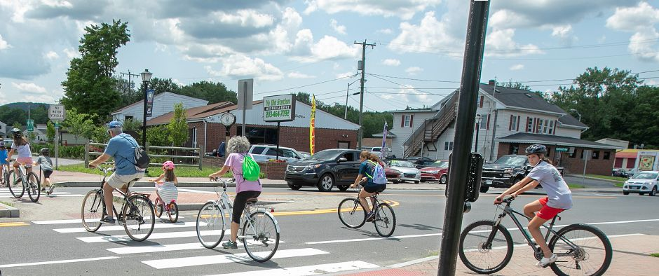 Bicyclists cross West Main Street on the Farmington Canal Heritage Trail in Cheshire, Thurs., July 25, 2019. Dave Zajac, Record-Journal