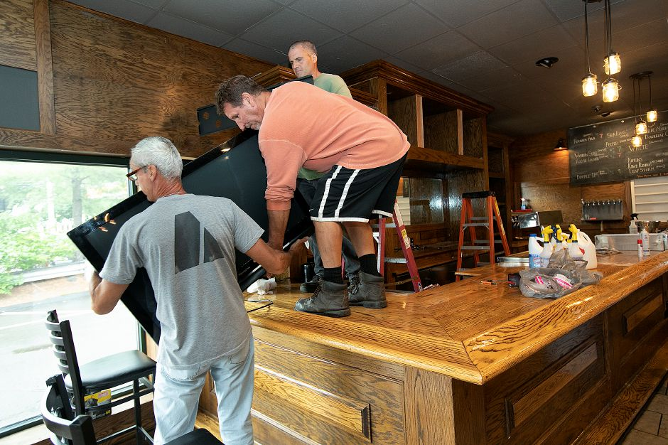 Helpers, left to right, Michael Hamm, Jim Palumbo and Dominic Malizia take a monitor down while cleaning up around the bar of the former Greer