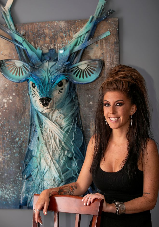 "Artist Stephanie Hongo, of Southington, stands next to her first trash sculpture of a stag, titled ""Yondu."""