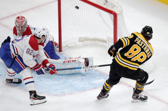 Boston Bruins right wing David Pastrnak (88) scores on Montreal Canadiens goaltender Carey Price during the first period of an NHL hockey game in Boston, Wednesday, Feb. 12, 2020. At left is Montreal Canadiens left wing Jonathan Drouin (92). (AP Photo/Charles Krupa)