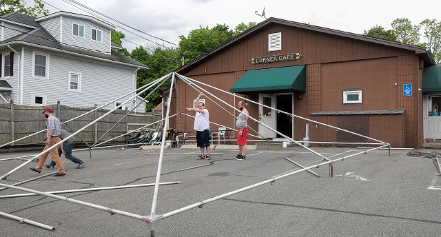 In this Monday, May 18, 2020 photo, workers from Old Saybrook based Tents 4 Your Events construct a tent in the side parking lot of Corner Cafe as they prepare for reopening in Yalesville, Conn. (Dave Zajac/Record-Journal via AP)