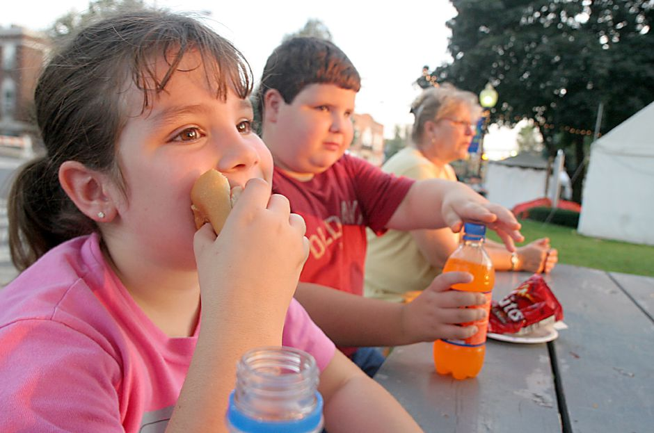 Record Journal Photo/ Johnathon Henninger 10.05.07 Casey Plourde, 6, eats a hotdog while her brother Andre Plourde, 7, reaches for his beverage during the Apple Harvest Festival Friday night.