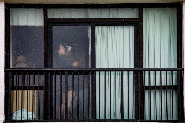 A woman holds her cat inside her condo in Garden City, S.C., as Isaias approached the Carolinas on Monday, Aug. 3, 2020. (Jason Lee/The Sun News via AP)