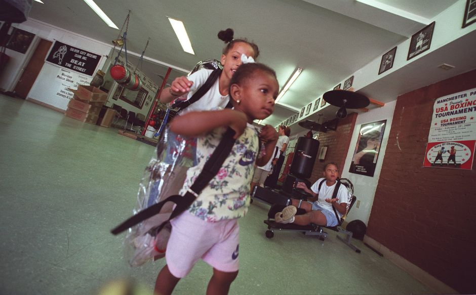 Chanday Robinson, 2, runs around the gym floor getting chased by a friend at the Silver City Boxing Club in Meriden Thursday morning Aug. 17, 2000. Chanday is trying to get the second strap of her new backpack onto her shoulder.