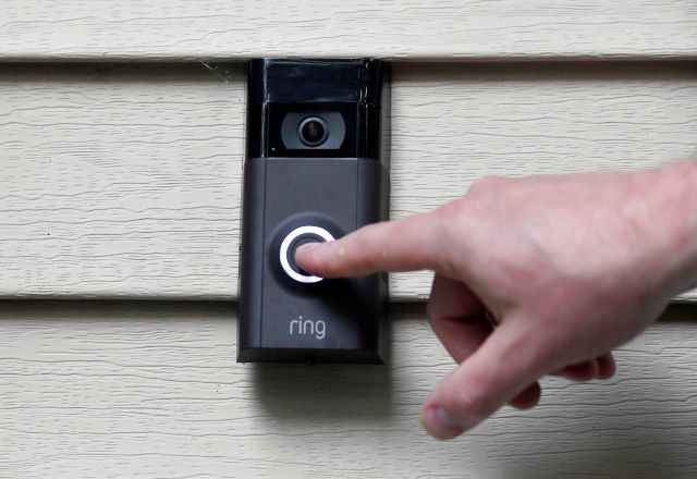 In this Tuesday, July 16, 2019, photo, Ernie Field pushes the doorbell on his Ring doorbell camera at his home in Wolcott, Conn. Southington police announced recently they will be using the Neighbors app, which works with the Ring cameras, to help solve and prevent crimes.  (AP Photo/Jessica Hill)