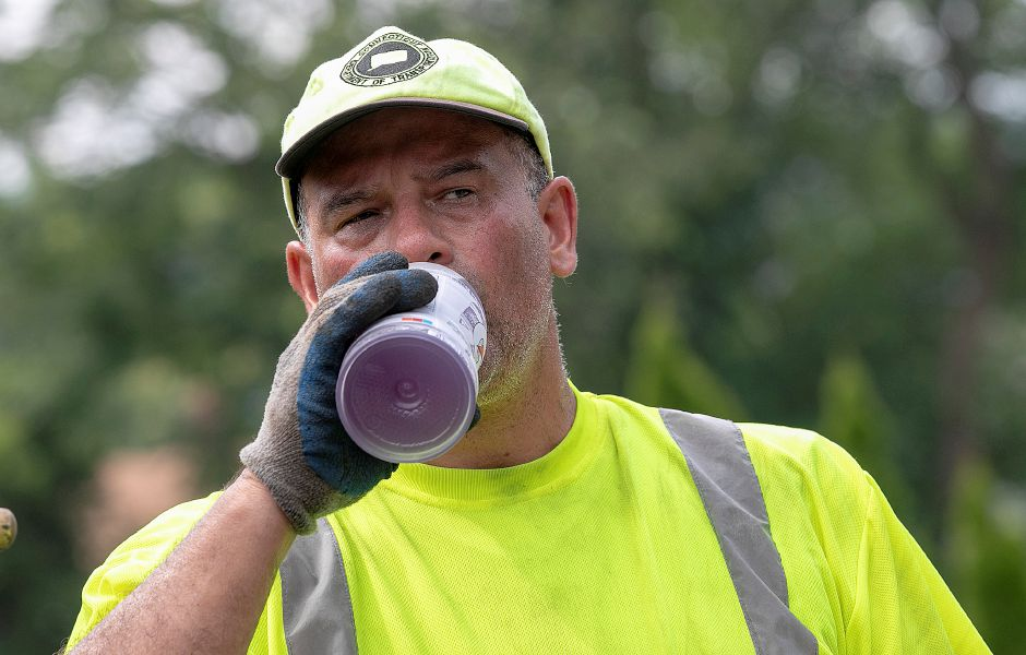 At left, a Connecticut Department of Transportation worker, who did not give a name, cools down with a cold drink Wednesday while working on Broad Street in Meriden.