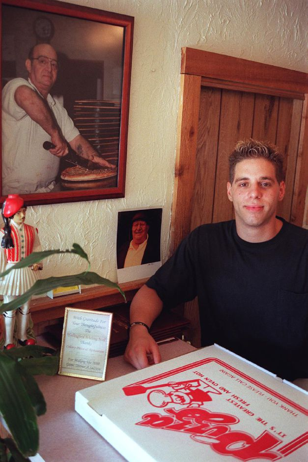 Mario Nicolaidis stands by a picture of his father, the late George Nicolaidis, inside Colony Pizza House on Center Street in Wallingford July 21, 2000.